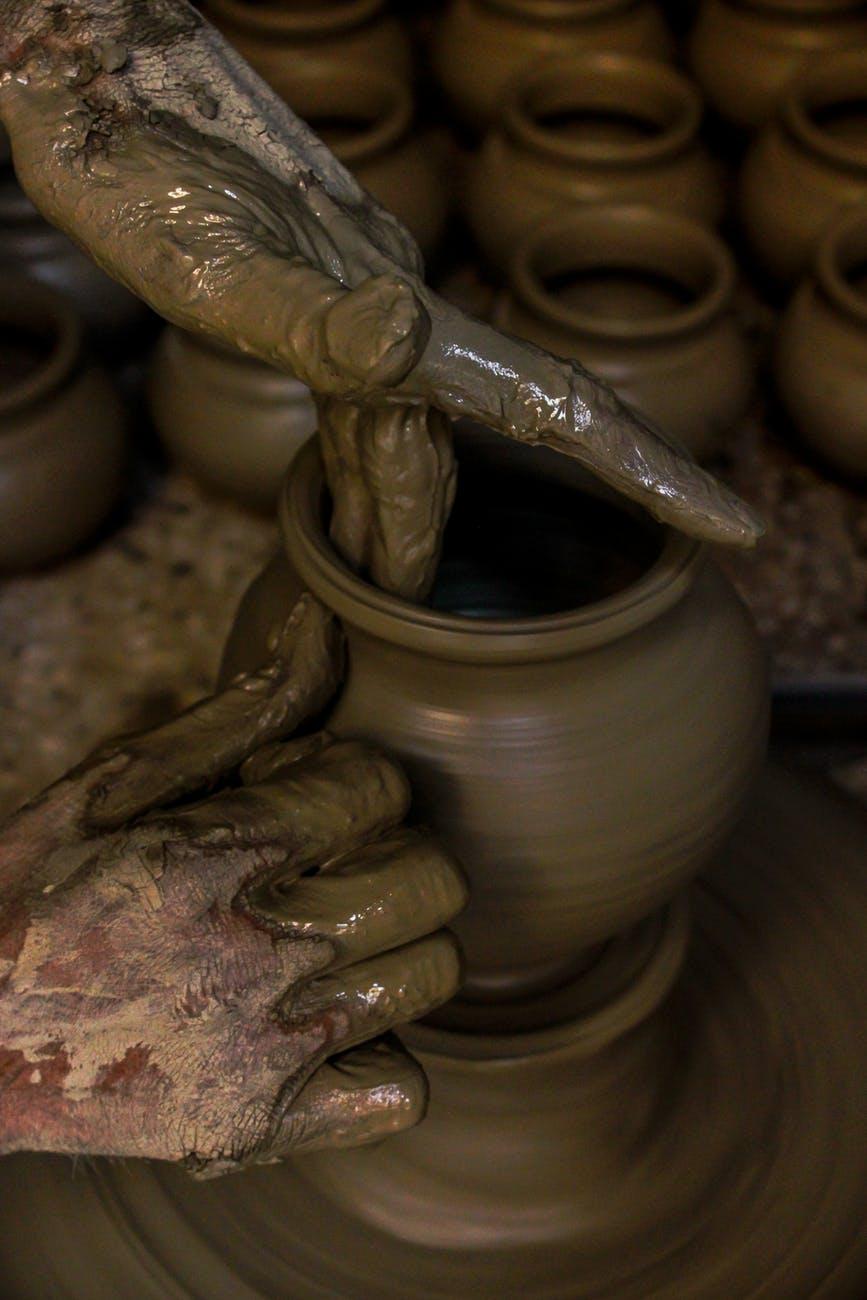 person molding brown clay pot